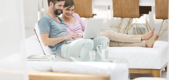 Image d'un couple assis sur un canapé faisant une recherche sur tablette dans un salon