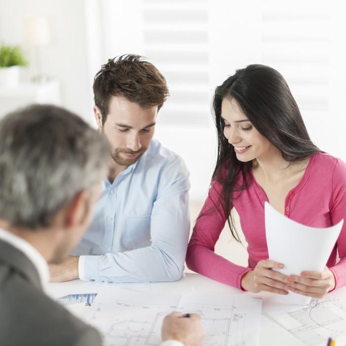 Image d'un couple se faisant conseiller par un professionel dans un bureau