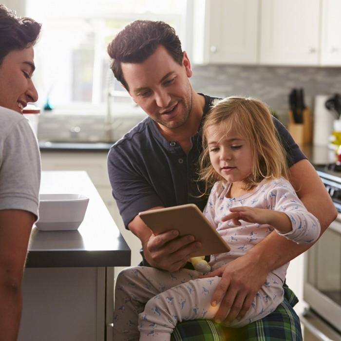 Famille dans une cuisine avec application mobile chaudière connectée