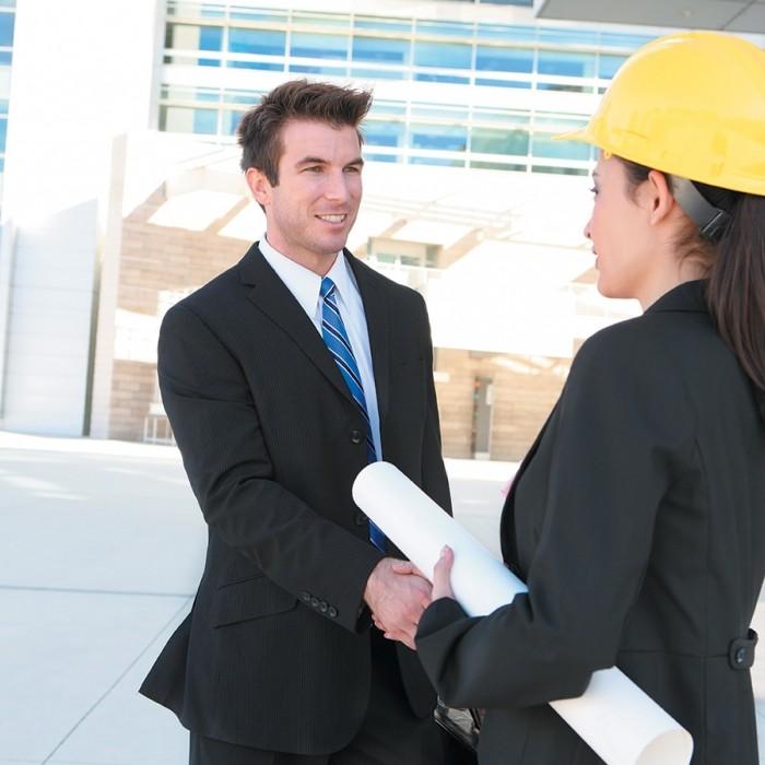 Image d'un homme et d'une femme architecte avec un casque de chantier se serrant la main devant un bâtiment